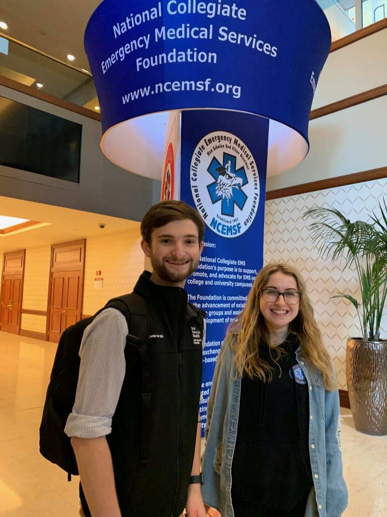 Quinnipiac University EMS members Charles Dunn and Cassidy Correia standing in front of NCEMSF sign at the 2020 NCEMSF conference