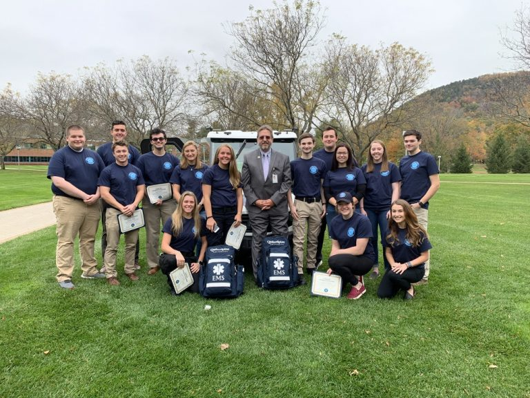 Members of QU EMS standing next to previous university medical director, Dr. Phil Brewer