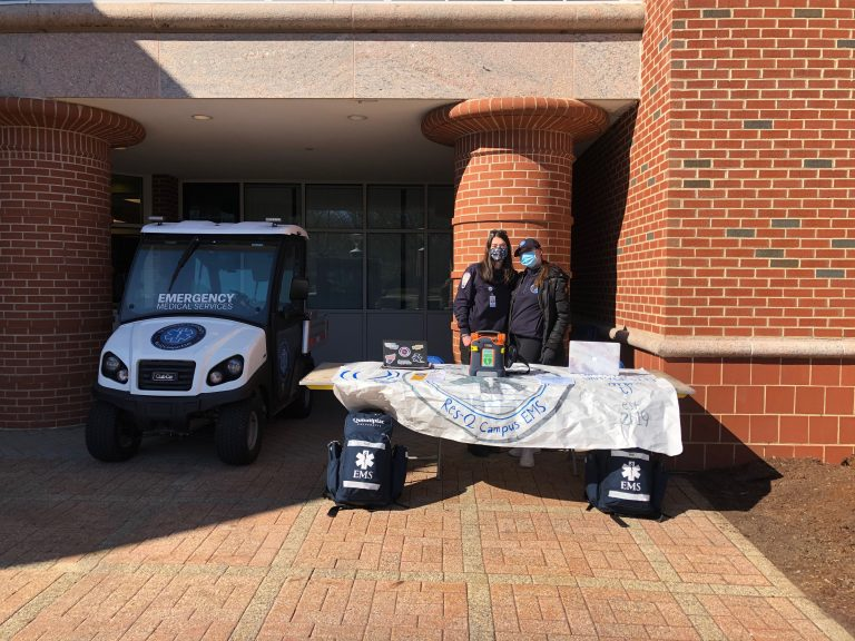 QU EMS members Kate Lobisser and Sophia Montoni standing next to QU EMS club car