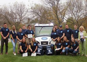 QU EMS Members and President Olian standing next to QU EMS Club Car